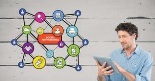 Mens die digitale tablet gebruiken tegen sociale media pictogrammen op achtergrond Royalty-vrije Stock Foto