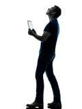 Mens die digitale tablet houden kijkend omhoog silhouet Stock Foto's