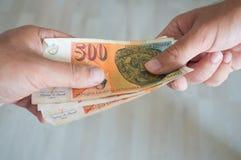 Mens die dinars geven aan een andere persoon Stock Afbeelding