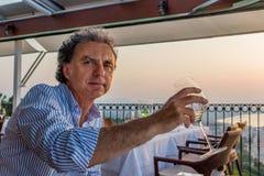 Mens die diner hebben die het overzees overzien bij zonsondergang royalty-vrije stock afbeelding