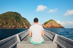 Mens die door boot naar tropisch eiland reizen royalty-vrije stock afbeeldingen