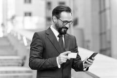 Mens die door creditcard op smartphone buiten bureau betalen Rijpe bedrijfsmensen die orde met creditcard maken telefonisch terwi royalty-vrije stock foto's