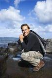 Mens die door de kust in Maui, Hawaï knielt. stock afbeelding
