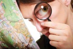 Mens die door een vergrootglas kaart bekijken Stock Foto's