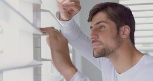 Mens die door venster blinde thuis 4k kijken stock footage