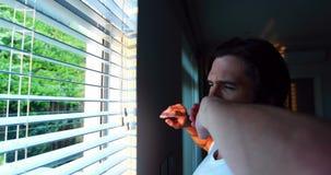 Mens die door vensterzonneblinden kijken na ontwaken stock footage