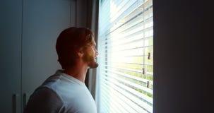 Mens die door vensterzonneblinden kijken na ontwaken stock video
