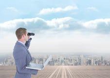 Mens die door verrekijkers tegen stadsachtergrond kijken stock foto