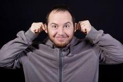 Mens die dwaas gezicht maken door zijn oren te trekken Stock Afbeeldingen