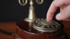 Mens die een aantal op een oude stijl retro roterende telefoon draaien stock footage