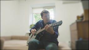 Mens die een akoestische gitaar speelt Mens die Akoestische Gitaar dicht omhoog langzame geanimeerde video spelen in de ruimte zi stock video