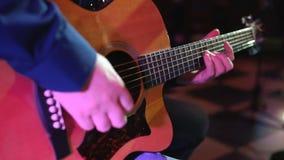 Mens die een akoestische gitaar speelt stock video