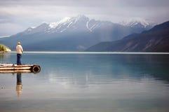 Mens die in een Alpien Meer vist royalty-vrije stock afbeelding