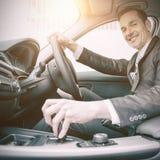 Mens die een auto drijven en bij camera glimlachen royalty-vrije stock foto's