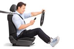 Mens die een auto drijven en zijn telefoon bekijken Royalty-vrije Stock Afbeelding
