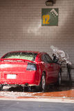Mens die een auto schoonmaakt Stock Foto's