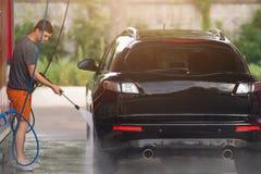 Mens die een auto wassen die een hoge druksysteem met behulp van stock foto's