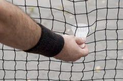 Mens die een badmintonshuttle nemen Stock Afbeeldingen