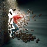 Mens die een bakstenen muur doornemen Stock Afbeelding