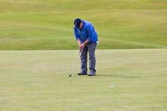 Mens die een bal zetten bij beroemde golfcursus StAndrews, Schotland Stock Foto's