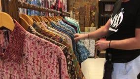 Mens die een Balinees batikoverhemd in de opslag kiezen Het winkelen voor mensen in het concept van Azië Katoenen overhemd stock video