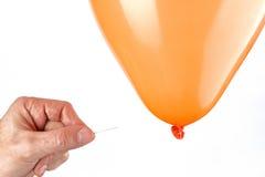 Mens die een ballon met een speld prikken Royalty-vrije Stock Foto's