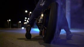 Mens die een banddoorsmelting op motorfiets op de stadsweg doen bij nacht Langzame Motie stock video