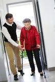 Mens die een bejaarde dame helpen die het huis ingaan Stock Afbeeldingen