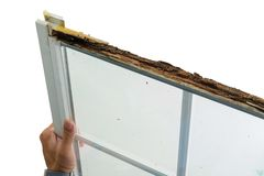 Mens die een beschadigd venster met natte verrotting houden stock fotografie
