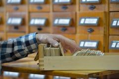 Mens die in een bibliotheekcatalogus zoeken Royalty-vrije Stock Foto's