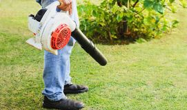 Mens die een bladventilator op het gazon van de tuin met behulp van stock foto's