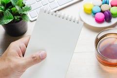 Mens die een boek en een toetsenbord met een hete kop thee, makaron op de lijst houden Royalty-vrije Stock Foto
