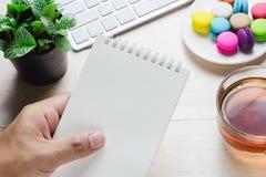 Mens die een boek en een toetsenbord met een hete kop thee, makaron op de lijst houden Royalty-vrije Stock Foto's