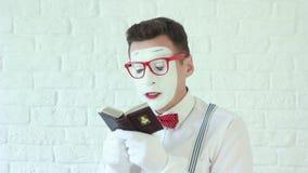 Mens die een boek en het lachen lezen pantomime stock videobeelden