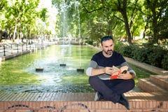 Mens die een boek in een park lezen stock afbeelding