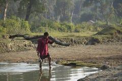 Mens die een boomstam dragen Stock Fotografie