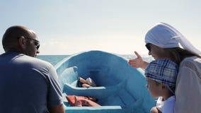 Mens die een boot draaien terwijl het spreken aan passagier stock videobeelden