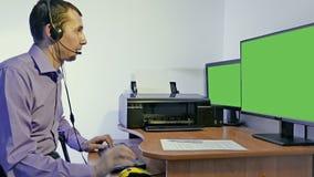 Mens die in een call centresteun werken voor computer met hoofdtelefoons en microfoon stock footage