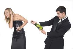 Mens die een champagnefles opent bij een partij Stock Afbeelding