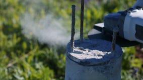 Mens die een concrete kolom snijden Vonken van metaal en concrete stofbouw stock video