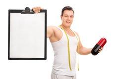 Mens die een dieetpil en een klembord houden Stock Fotografie