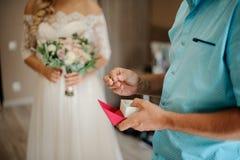 Mens die een doos met trouwringen en bruid op de achtergrond houden Royalty-vrije Stock Foto