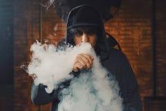 Mens die een elektronische sigaret vaping Stock Afbeeldingen