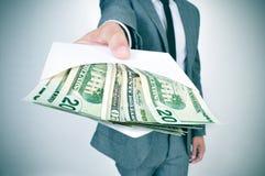 Mens die een envelophoogtepunt van Amerikaanse dollarrekeningen geven Royalty-vrije Stock Afbeelding