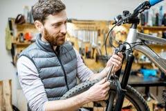 Mens die een fiets in de workshop herstellen stock foto's