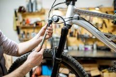 Mens die een fiets in de workshop herstellen royalty-vrije stock foto's