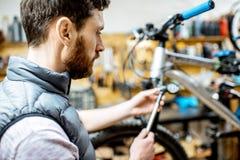 Mens die een fiets in de workshop herstellen stock afbeeldingen