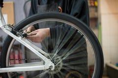 Mens die een fiets herstellen Stock Foto's