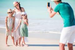 Mens die een foto van zijn familie op het strand nemen stock foto