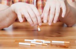 Mens die een gebroken sigaret houden stock afbeeldingen
